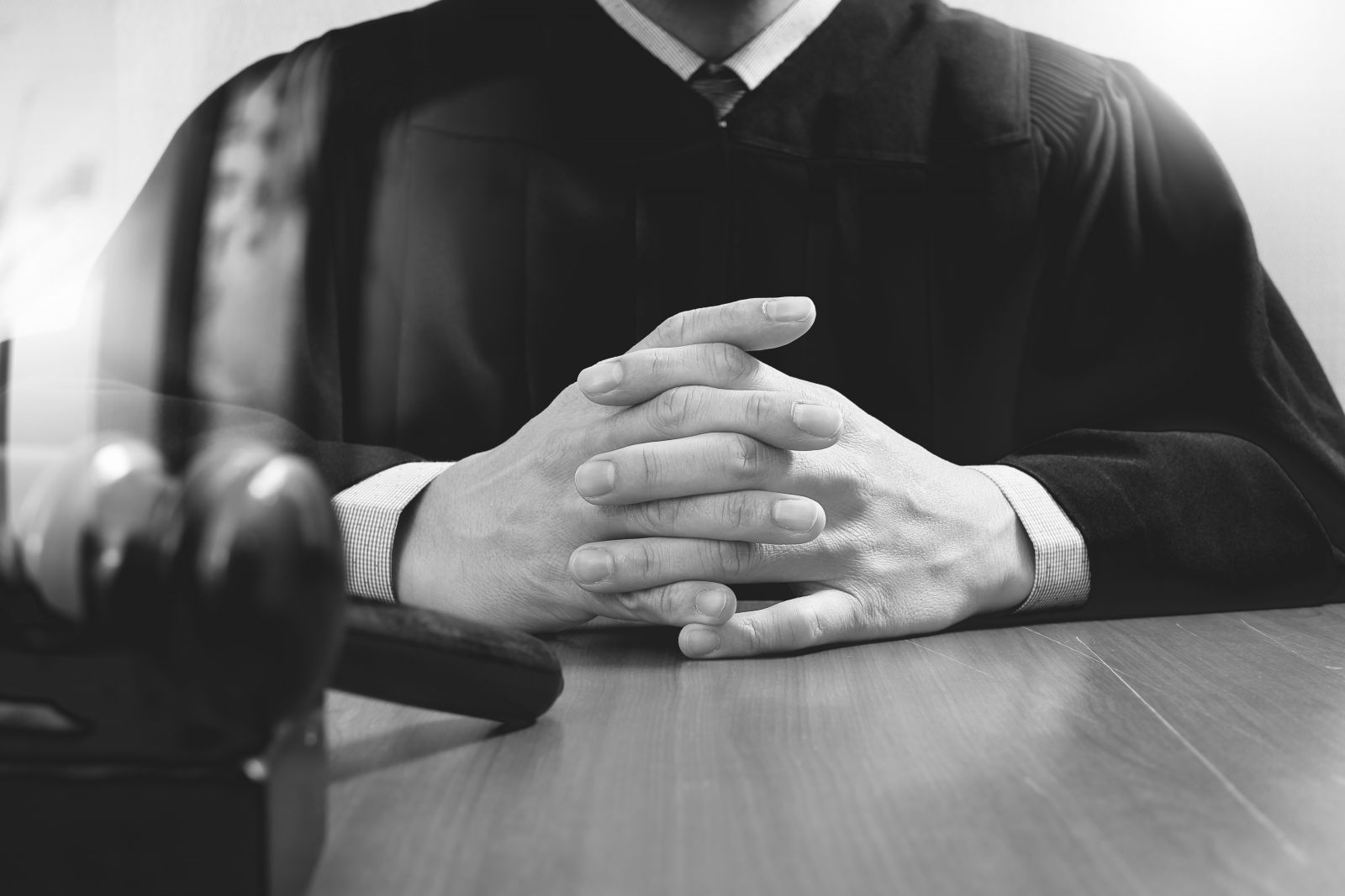 Male judge in a courtroom striking the gavel,working with digital tablet computer docking keyboard. Justice and law concept banner image